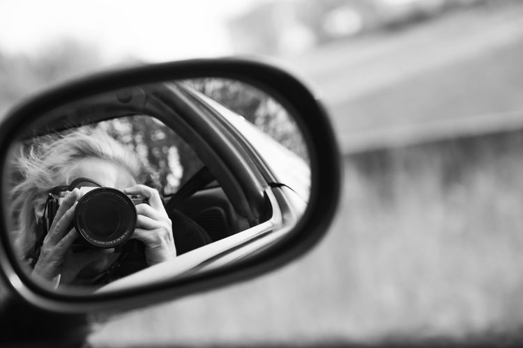 Reflection of man photographing on side-view mirror