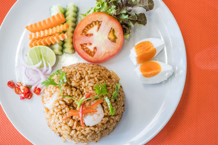 Top View of fried rice with shrimp and fresh vegetable, salted eggs put on the white plate and orange table Close-up Cucumber Day Food Food And Drink Freshness Fried Egg Healthy Eating Indoors  No People Plate Ready-to-eat Rice - Food Staple Seafood Serving Size Tomato Vegetable