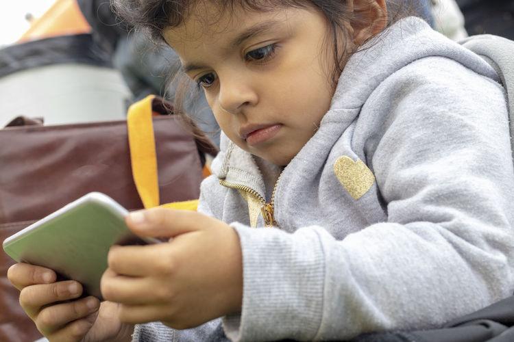 Close-Up Of Cute Girl Using Phone