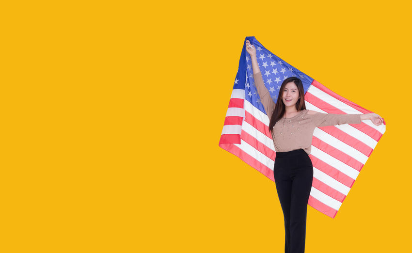 Low angle view of woman standing against yellow background