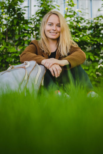 Portrait of smiling young woman with blond hair sitting on grass