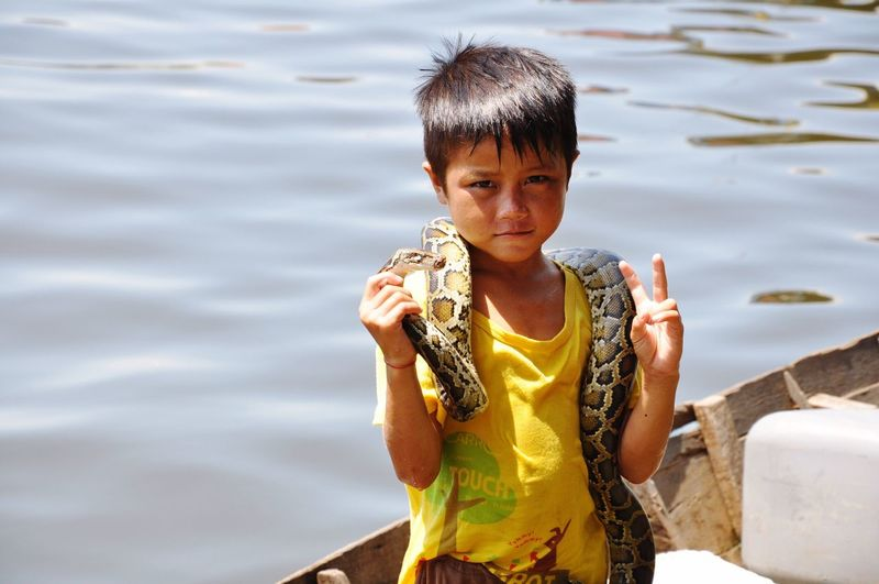 Portrait of cute boy holding snake while showing peace sign on boat against lake