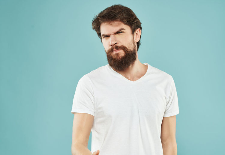 Young man looking away against blue background