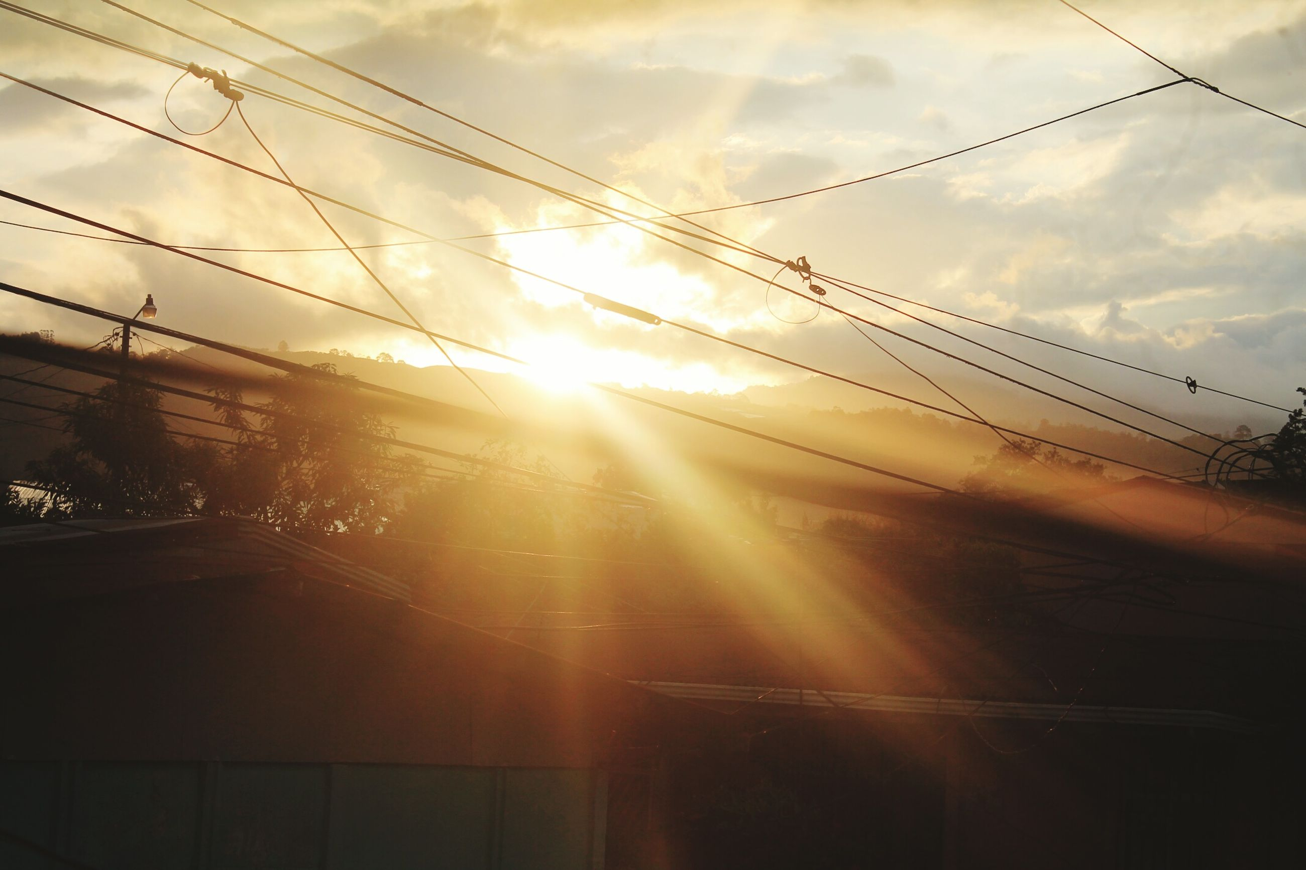 sun, sky, sunbeam, lens flare, sunlight, power line, sunset, transportation, built structure, electricity pylon, cable, building exterior, cloud - sky, architecture, silhouette, car, mode of transport, cloud, street, outdoors