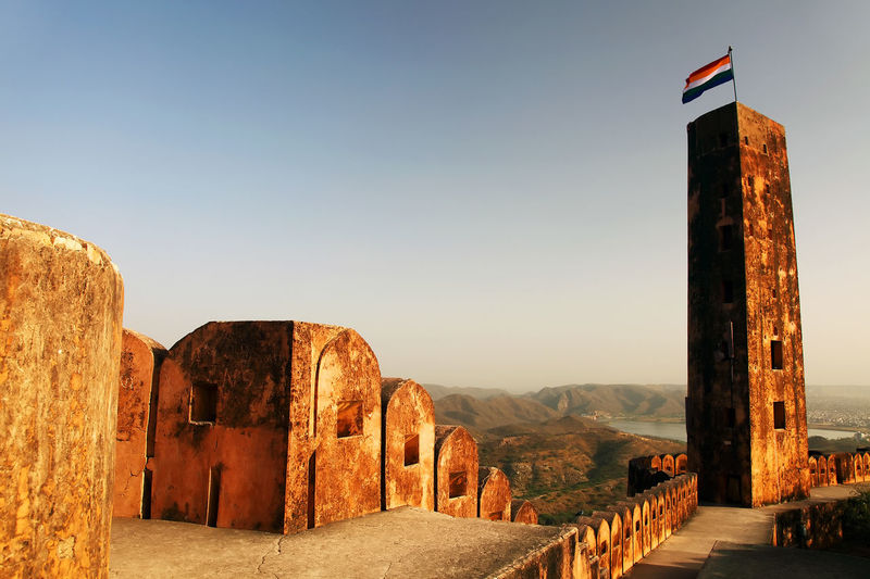 Indian flag on column at jaigarh fort against clear sky