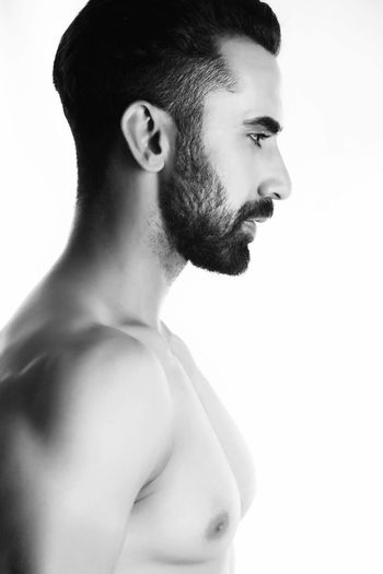 Side view of shirtless young man looking away while standing against white background