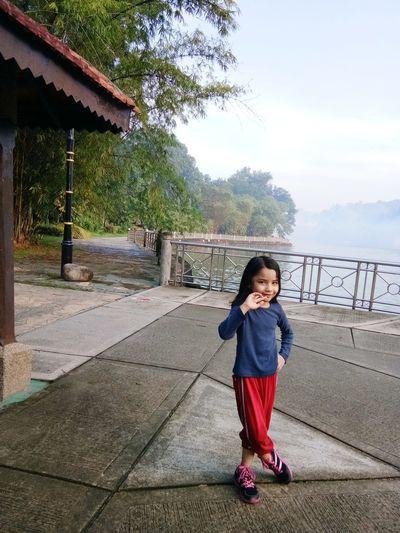 Full length portrait of cute girl standing outdoors