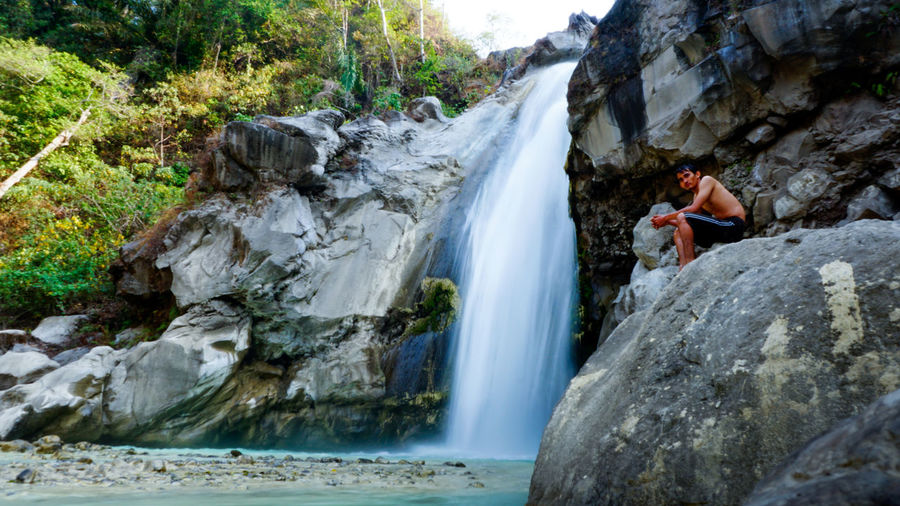 Low angle view of man sitting on rock against waterfall