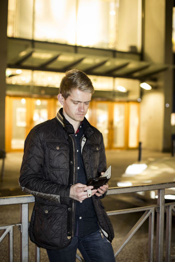 Young Man Using Mobile Phone While Standing By Railing