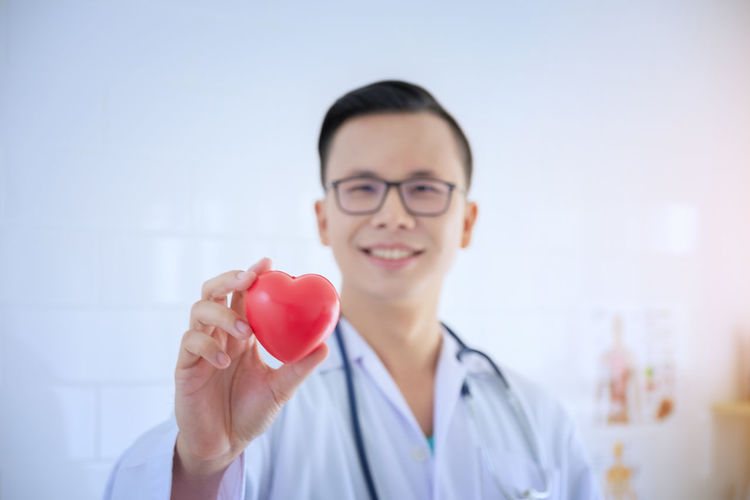 Portrait Of Smiling Male Doctor Holding Heart Shape Stress Ball At Hospital