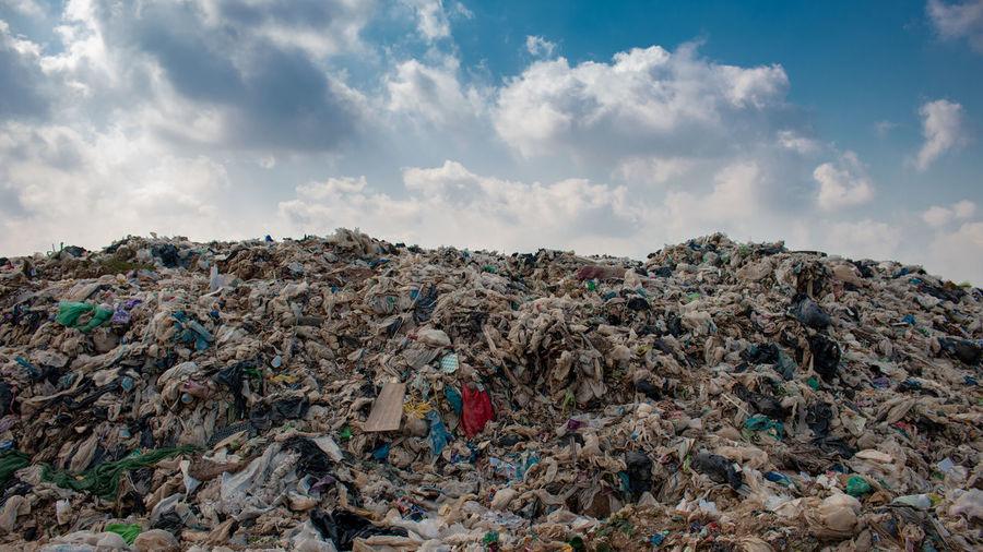 Stack of garbage on rock against sky