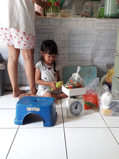 Cute girl weighing vegetables while sitting by mother at home