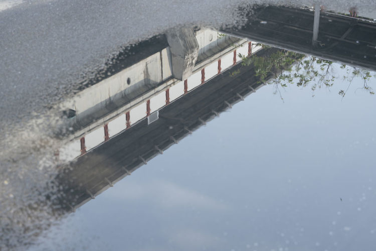 Reflection of bridge on water in puddle
