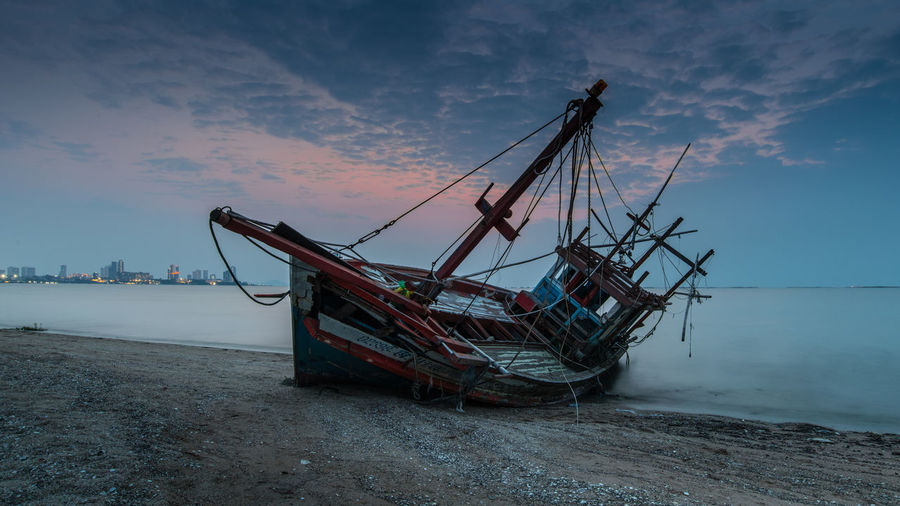 Abandoned ship moored at beach against sky