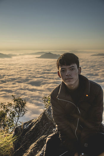 Portrait of young man sitting on mountain peak during sunrise