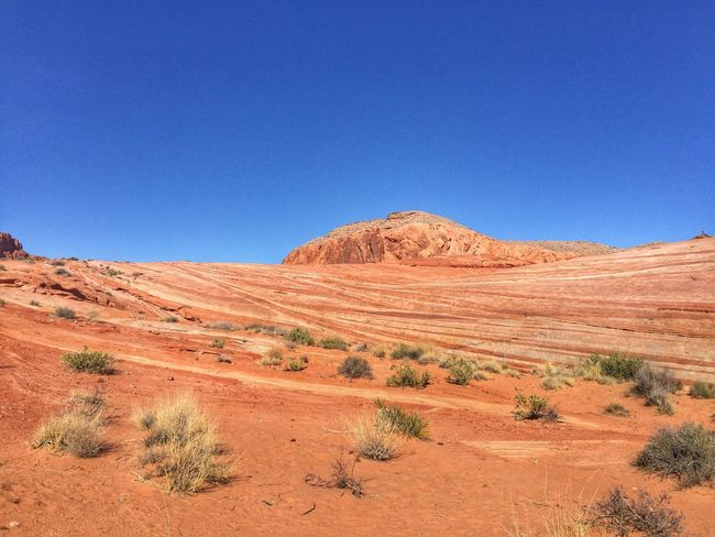Low angle view of large striped orange sandstone hill No Filters Or Effects Blue Tranquil Scene Nature Arid Climate Landscape Clear Sky Scenics Rock - Object No People Outdoors Tranquility Beauty In Nature Day Extreme Terrain Desert
