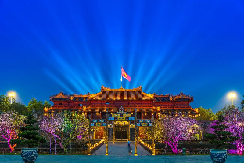 Illuminated temple against blue sky at night