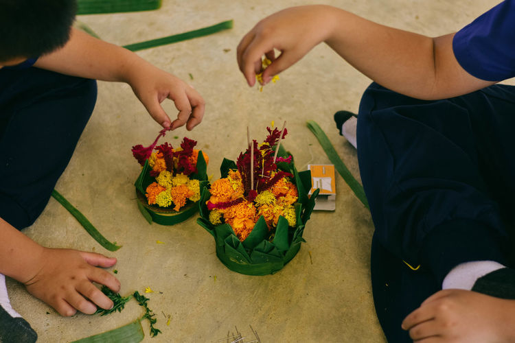 High angle view of people arranging flowers