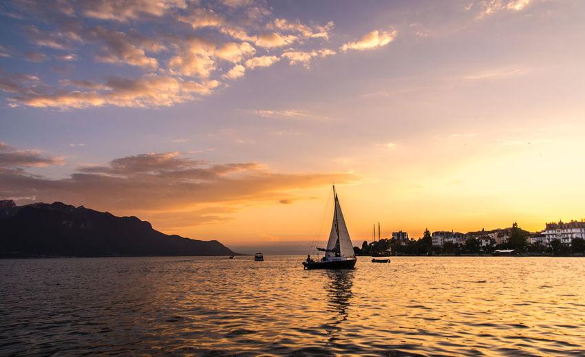 Boat sailing in sea at sunset
