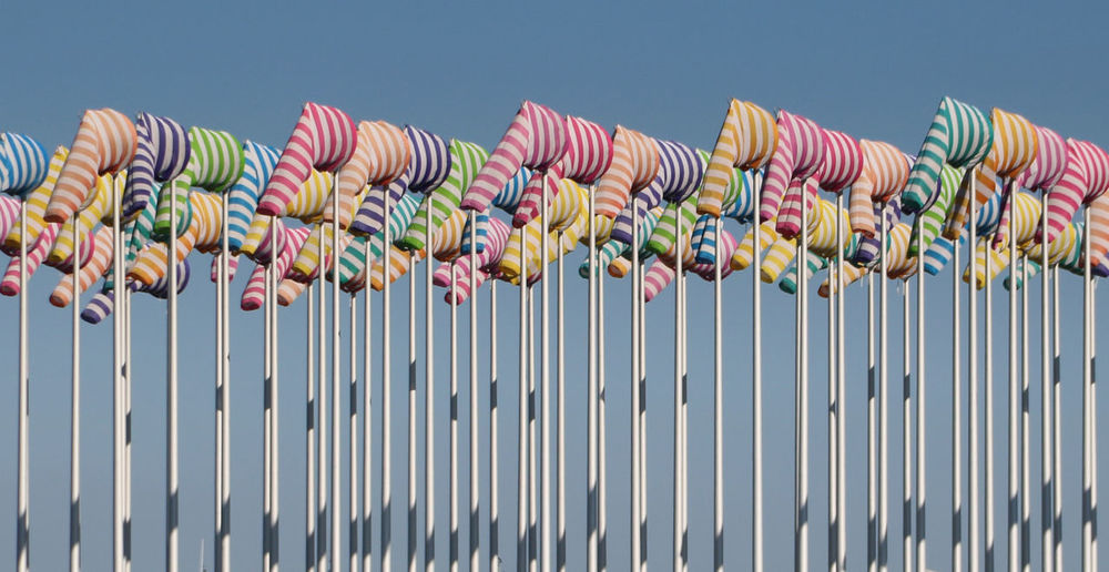 Low angle view of colorful windsocks against clear sky