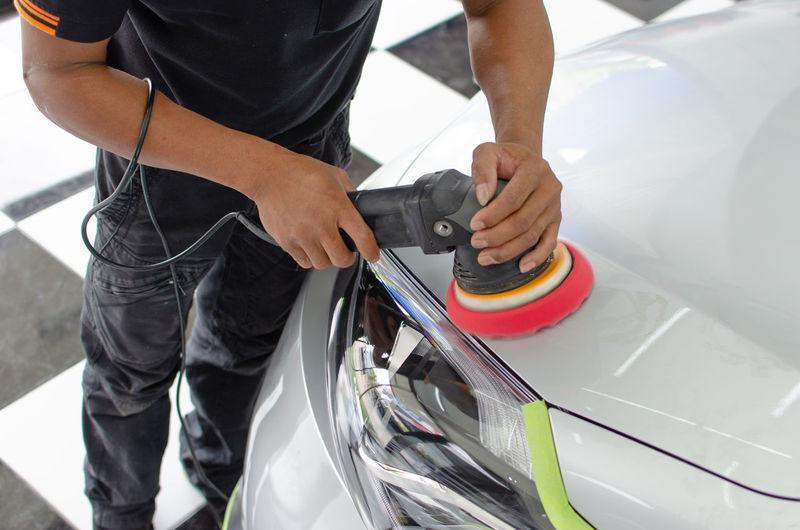 High Angle View Of Mechanic Polishing Car