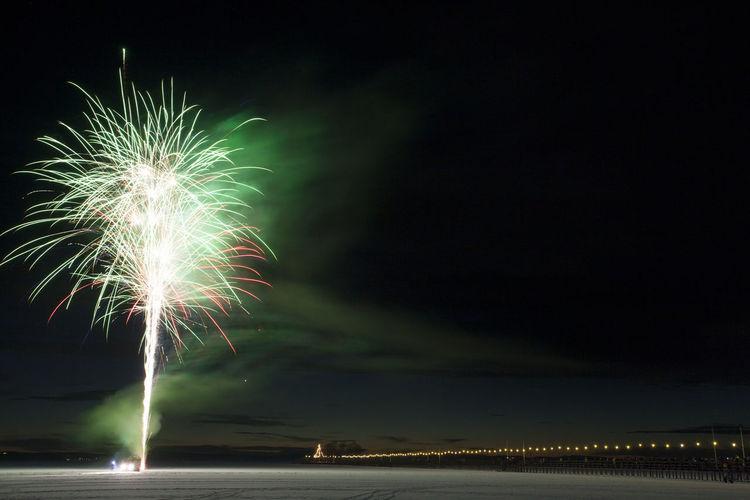 Firework exploding over landscape against sky at night