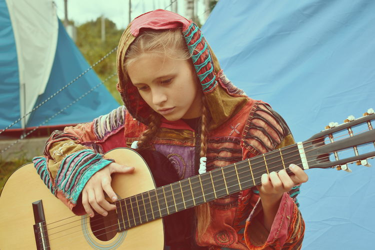 Cute girl playing guitar outdoors