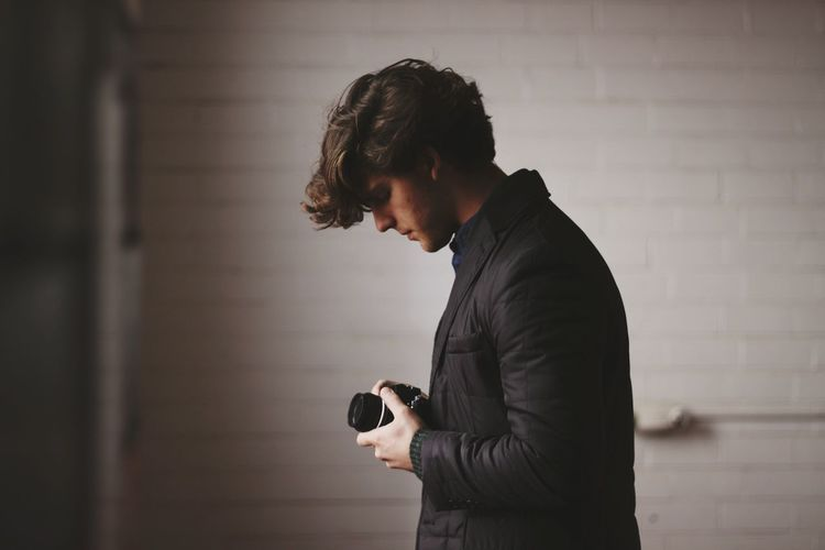 Side view of man using camera