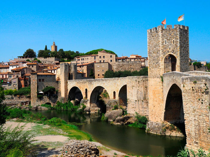 View of the medieval village of Besalu in Girona - Spain Antique Besalú Castle Catalonia Girona SPAIN Sightseeing Travel Ancient Arch Architecture Bridge Bridge - Man Made Structure Building Exterior Built Structure History Landscape Medieval Outdoors Picturesque River Tower Town Village Water