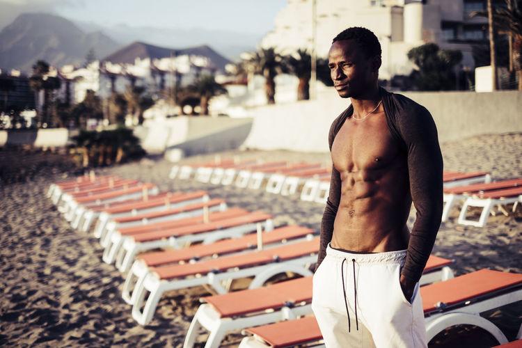 Muscular man standing at beach