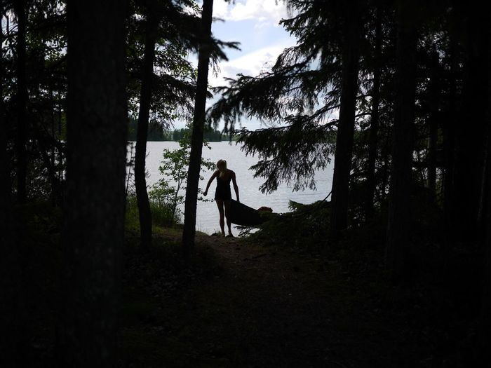 Silhouette man in forest against sky
