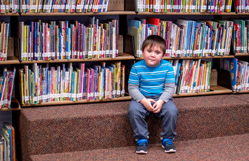 A little boy sits among picture books at a library, waiting for a story