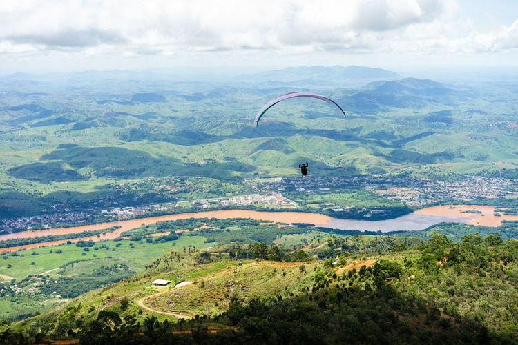 Paraglider is flying in Brazil, aerial view. Adventure Beauty In Nature Cloud - Sky Day Environment Extreme Sports Flying Freedom Land Landscape Leisure Activity Mid-air Nature Non-urban Scene Outdoors Parachute Paragliding River Scenics - Nature Sky Skydiving Sport Tranquil Scene Unrecognizable Person Valadares