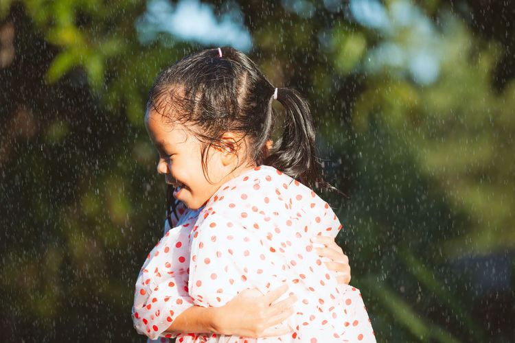 Sisters wearing raincoats embracing in park during rainfall