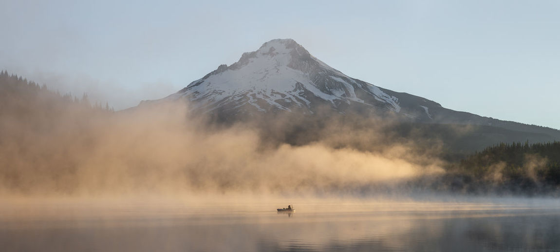 Panoramic view of boat in lake by snowcapped mountain against sky