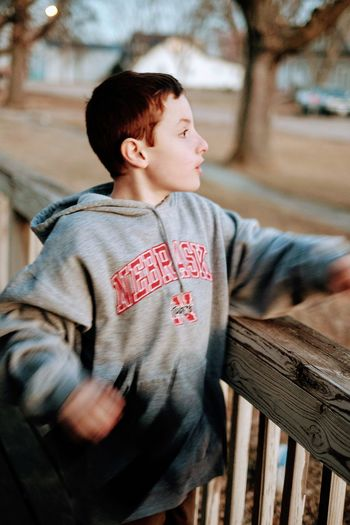 Boy looking away while standing by wooden railing