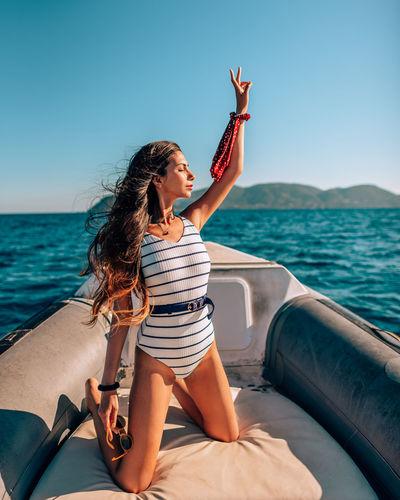 Woman with arm raised kneeling in nautical vessel on sea against sky
