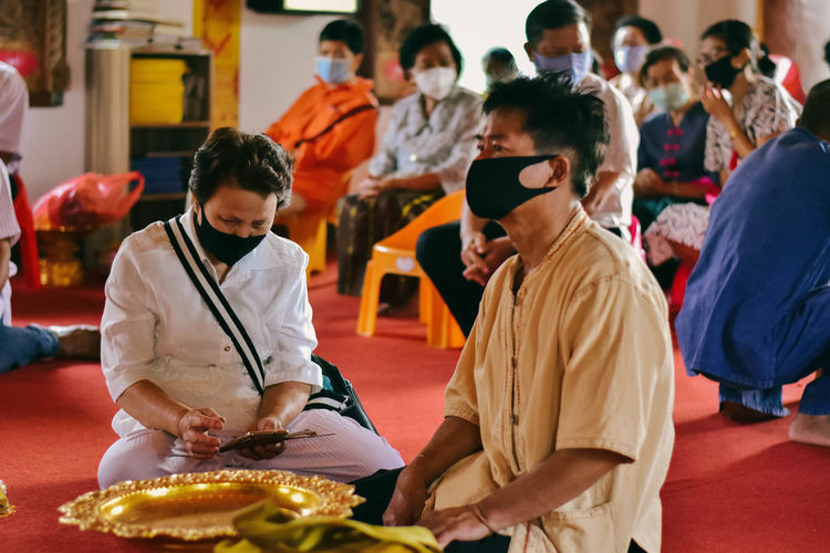 People wearing mask sitting at temple