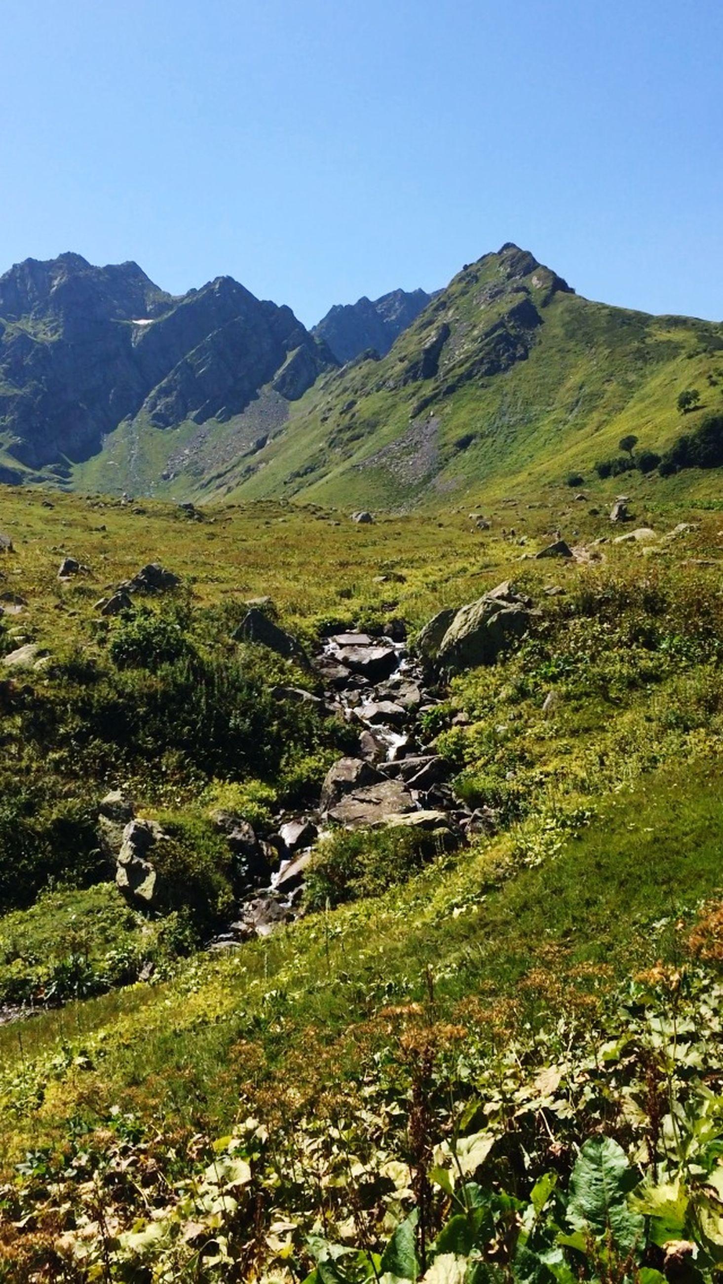 mountain, tranquil scene, grass, landscape, tranquility, clear sky, scenics, beauty in nature, mountain range, nature, non-urban scene, green color, rock - object, field, remote, stream, plant, idyllic, sky, grassy