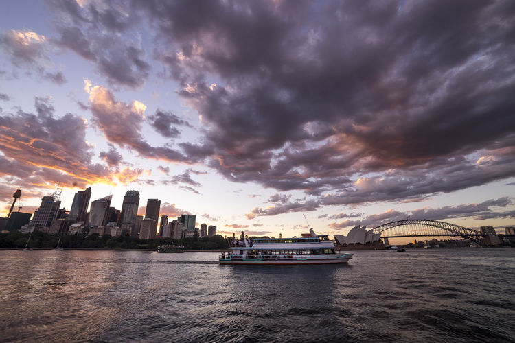 Ferry By Sydney Harbor Bridge And Opera House Against Sky During Sunset