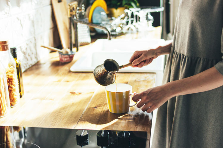 Midsection of woman pouring coffee into cup on table at home