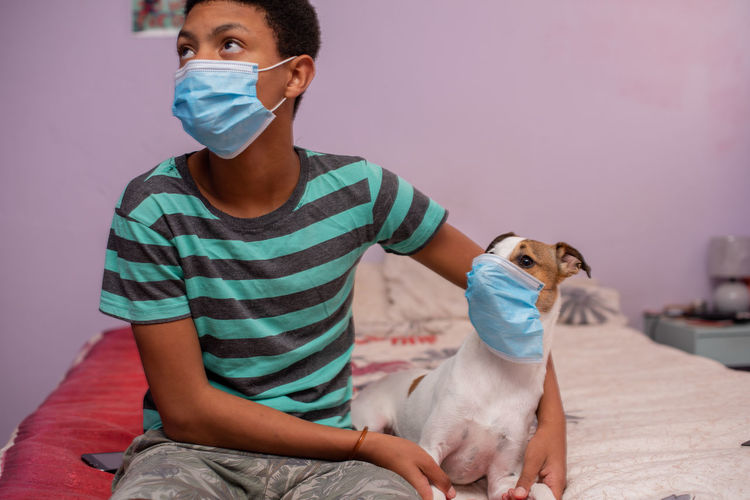 Portrait of young boy and his dog wearing a mask