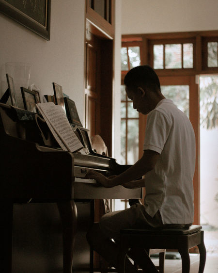 Side view of man playing piano at home