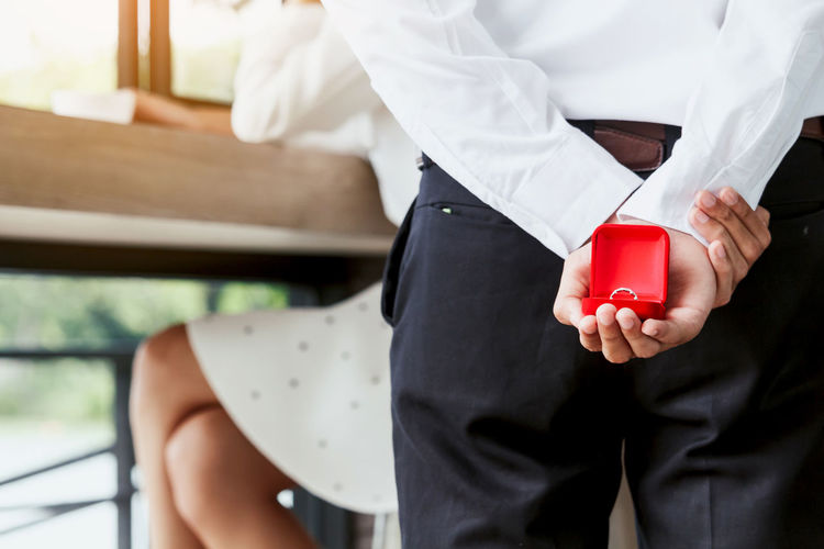 Midsection Of Man Holding Wedding Ring With Girlfriend Sitting At Table