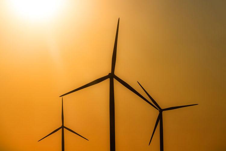 Low angle view of wind turbine against orange sky