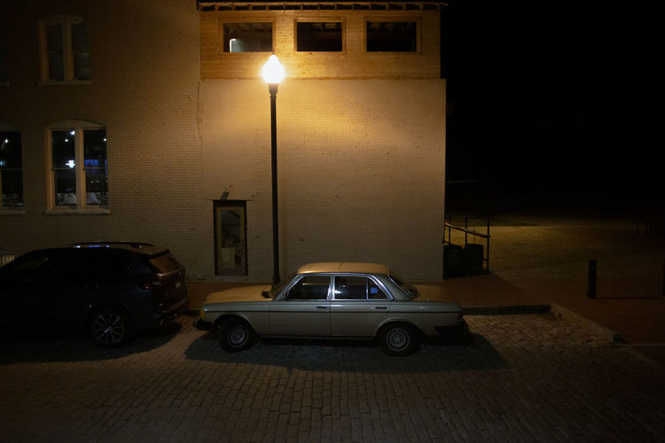 Cars parked on illuminated street by building at night