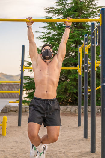 Young man wearing flu mask exercising outdoors