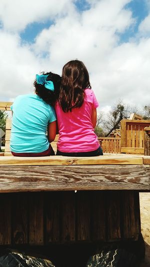 Rear View Of Siblings Sitting On Bench