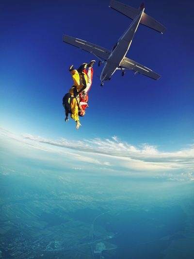 Low Angle View Of Skydivers Jumping From Airplane