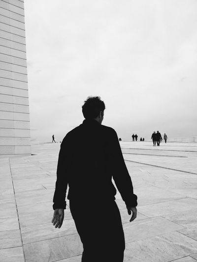 Rear view of man walking at oslo opera house against sky